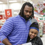 Reairra Marks, 10, talks with Pettigrew during the shopping spree. The kids, selected for good grades and behavior, each got $300 to spend.