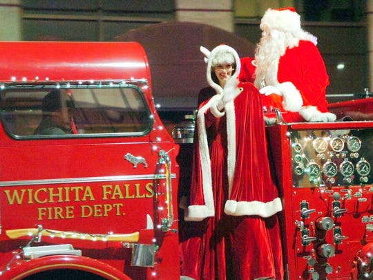 Mr. and Mrs. Claus board an antique truck at City Lights in 2013.