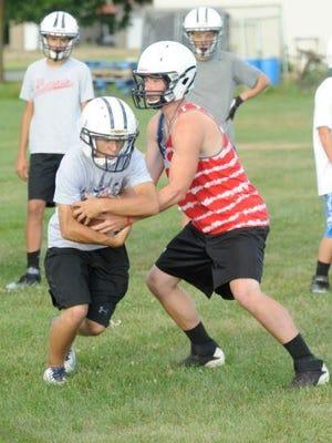 Roncalli's Evan Jagemann, left, and Brett Bahrs work on a handoff while practicing on Tuesday, Aug. 4.