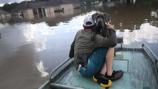SORRENTO, LA - AUGUST 17: Travis Guedry and his dog Ziggy glide through floodwaters keeping an eye out for people in need on August 17, 2016 in Sorrento, La.