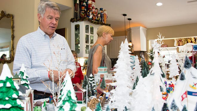 Paul and Luci Regensdort admire an intricate Christmas village during the Holiday Home Tour.