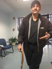 Jason Breitenfeld, victim of a drunken driving crash in 2013, walks with the help of a cane.