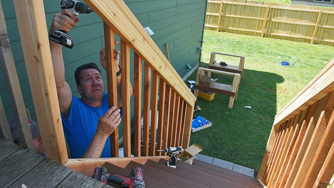 "Dave Serck, right, a volunteer from Flooring America, and Mark Swenson, a volunteer from Great Western Bank, work on the railing for a set of stairs for Robin Henry's deck as part of the Home Builders Association of the Sioux Empire's Repair Affair event Tuesday, June 7, 2016, at Henry's house in Tea, S.D. Henry said the steps will allow her 8-year-old daughter Lanie, who walks walks and runs on her knees because of a rare genetic disorder, to access their backyard on her own. ""This allows her to be more independent,"" Henry said."