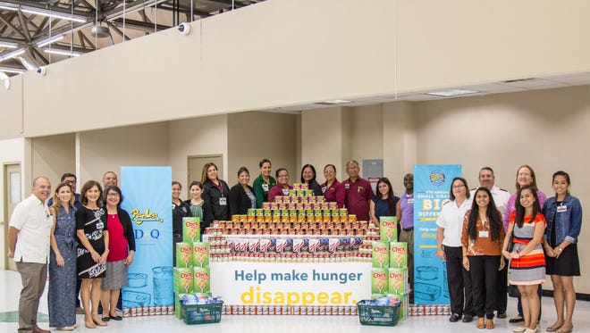 Officials and employees of Pay-Less Markets, and representatives of non-profit groups, stand near an informational display for the store's annual donation program to fight hunger.