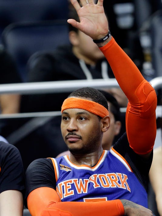 FILE - In this March 1, 2017, file photo New York Knicks' Carmelo Anthony waves to fans cheering his name during the final moments of an NBA basketball game against the Orlando Magic in Orlando, Fla. The Knicks agreed to trade Anthony to the Thunder on Saturday, Sept. 23, 2017, saving themselves a potentially awkward reunion next week with the player they'd been trying to deal since last season.  New York will get Enes Kanter, Doug McDermott and a draft pick, a person with knowledge of the deal said. The person spoke with The Associated Press on condition of anonymity because the trade had not been announced.  (AP Photo/John Raoux, File)
