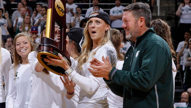 Leah O'Connor holds the trophy as coach Walt Drenth, right, stands by as the national champion Michigan State cross country team is honored during a men's basketball game against Santa Clara on Monday, Nov. 24, 2014, in East Lansing, Mich. Drenth announced his retirement on Monday after 16 seasons with Michigan State athletics, the last 14 as the director of track and field and cross country.