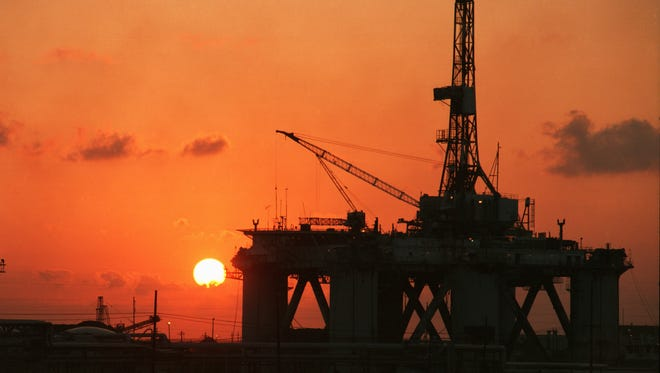 The sun sets behind one of the three rigs in Port Arthur.