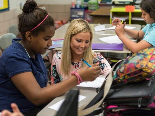 Seventh grader Sharya Johnson receives help on a math program from her teacher Megan Beard at Perry Heights Middle School.