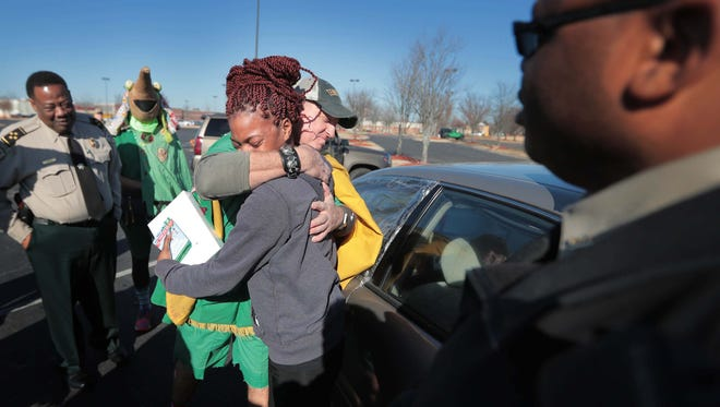 Kiaunna Johnson tears up as she receives a new Ipad compliments of the Shelby County Sheriff's Department, Target and the Order of Boll Weevils Monday morning during a surprising traffic stop near Wolfchase as part of their annual Christmas cheer project.