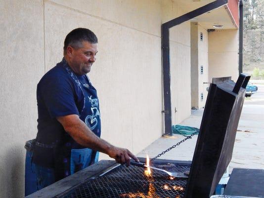 Shane Holder, Ruidoso School Board Secretary, flips burgers.