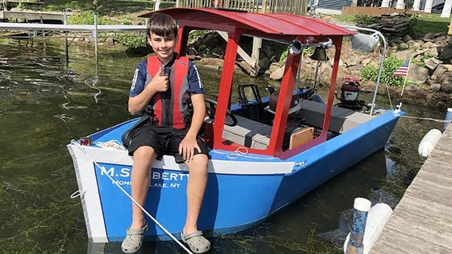 Josh Gleason, 14, sits on the boat he built after school closed in March due to COVID-19. The Naples student, entering the ninth grade, built the boat from the ground up.
