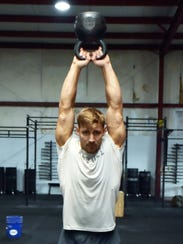 Alex Anderson works out with kettle bells.