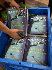 A South Korean employee displays copies of Harper Lee's