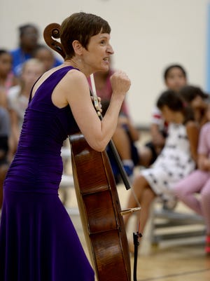 """Kids listen as Elizabeth Gottling Mendoza tells a story about a piece she called """"spy music"""" during a Thursday performance of the Chanticleer String Quartet at the Boys & Girls Clubs of Wayne County."""
