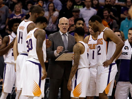 Suns interim head coach Jay Triano speaks with his
