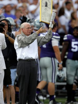 Kansas State head coach Bill Snyder waves to fans while holding his College Football Hall of Fame induction before an NCAA college football game against South Dakota in Manhattan, Kan., Saturday, Sept. 5, 2015. (AP Photo/Orlin Wagner)