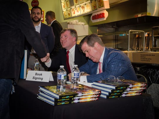 "Michael Cass, left, and former Mayor Karl Dean, authors of ""Nashville: The South's New Metropolis,"" sign copies of the book during a signing at the Nashville Farmers' Market."