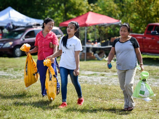 Sunita Limbu, center walks with mother Budha Limbu, left  and aunt Bishnu Subba as they shop for live chickens at the Mexican Market in Triune, Tenn., Saturday, Aug. 26, 2017.