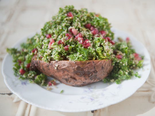 Stuffed sweet potato with kale, quinoa, and pomegranite