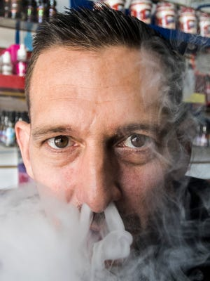About It All Vapors owner Tony Myers, of Hanover puffs a cloud of vape, while posing for a photo at his shop Tuesday, Sept. 27, 2016. Myers closed his shop recently. Amanda J. Cain photo
