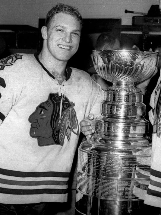 """FILE - In this April 16, 1961, file photo, Chicago Blackhawks left wing Bobby Hull smiles in the dressing room after defeating the Detroit Red Wings to win the Stanley Cup in Detroit. The names of Hockey Hall of Famers like Gordie Howe, Maurice """"Rocket"""" Richard and Hull will be removed from the Stanley Cup to make room for the next generation of champions. When a new layer is added to the 126-year-old trophy, the championship teams from 1954-65 will need to be removed so the trophy doesn't grow too big to travel. (AP Photo)"""