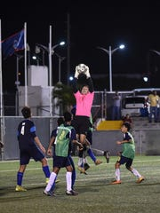 Goalkeeper Sean Evans of the Harvest Christian Academy Eagles makes one of his 11 saves to help his team defeat the St. Paul Warriors in an IIAAG Boys' Soccer League semifinal playoff match at the Guam Football Association National Training Center in Harmon on Dec. 16.