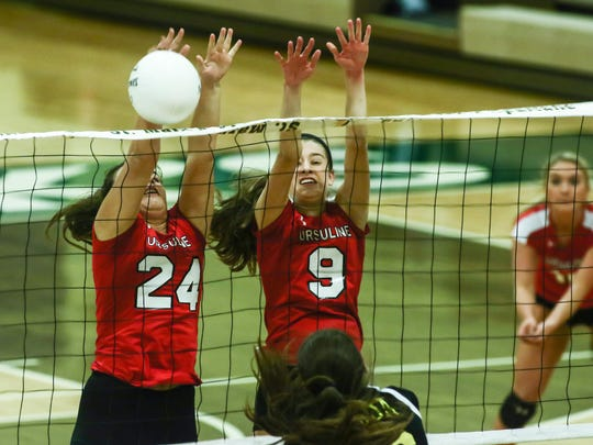 Grace Nordmeyer (24) and Abigail Rzucidlo (9) of Ursuline jump to block a spike during last year's state tournament. The Raiders are No. 1 in the volleyball rankings.