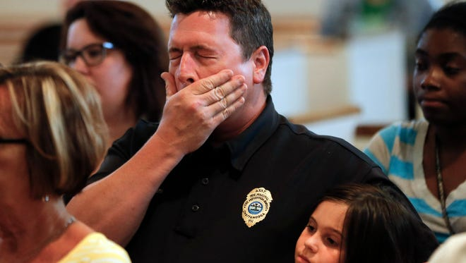 Chuck Hartung holds his daughter Haley, 8, during a prayer service at Wesley Memorial United Methodist Church for the victims of shootings at a recruiting center and another U.S. military site a few miles apart in Chattanooga on Thursday.