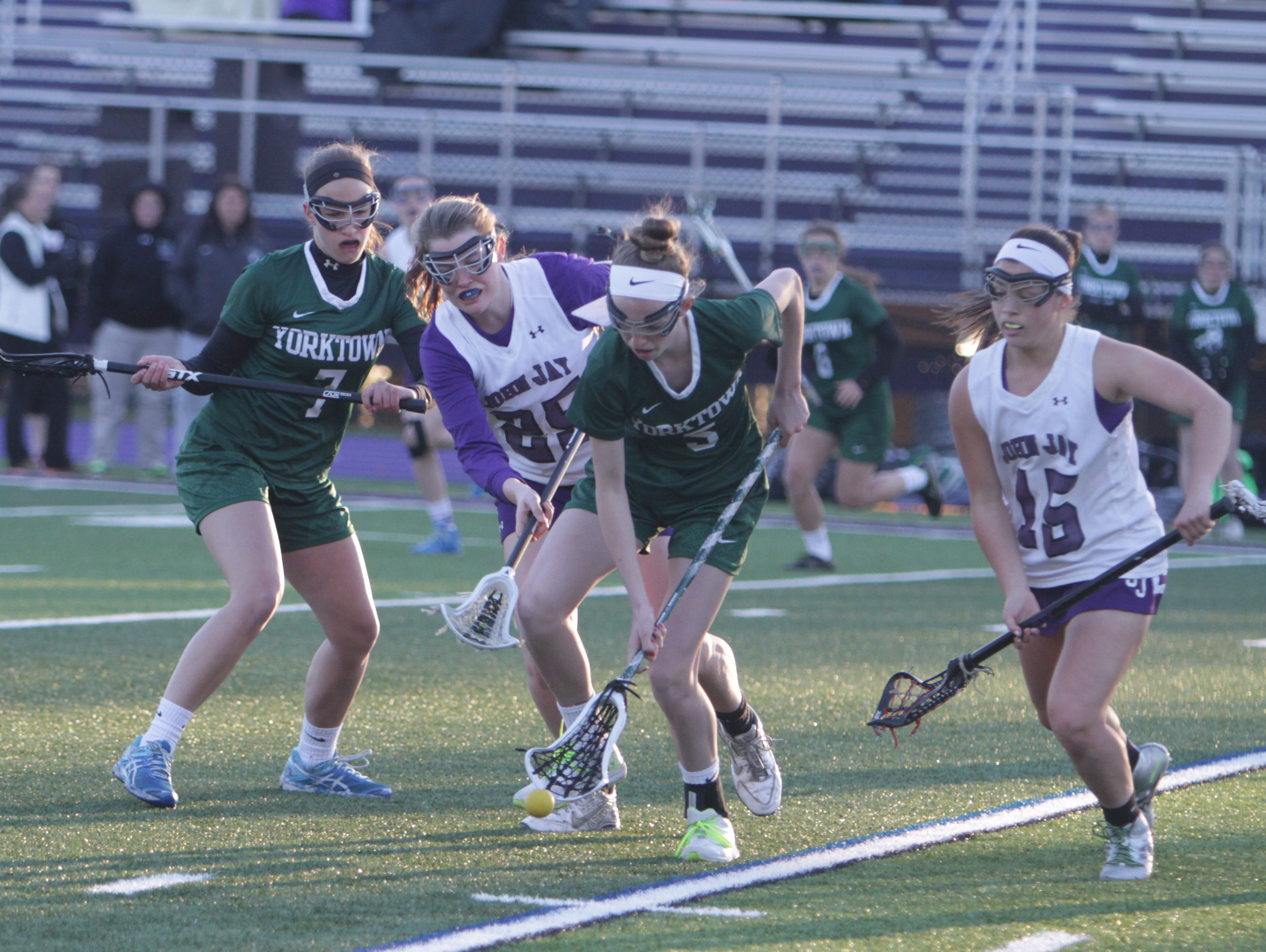 Yorktown's Ciara Frawley (green) attempts to scoop up a ground ball ahead of John Jay's Danielle Galea (25) during a Section 1 girls lacrosse game at John Jay-Cross River High School on Tuesday, March 29th, 2016. Yorktown won 15-5.