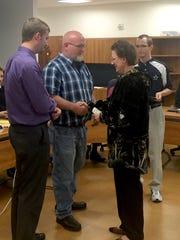 Jodi Kuzo presents a $1,500 check in memory of her