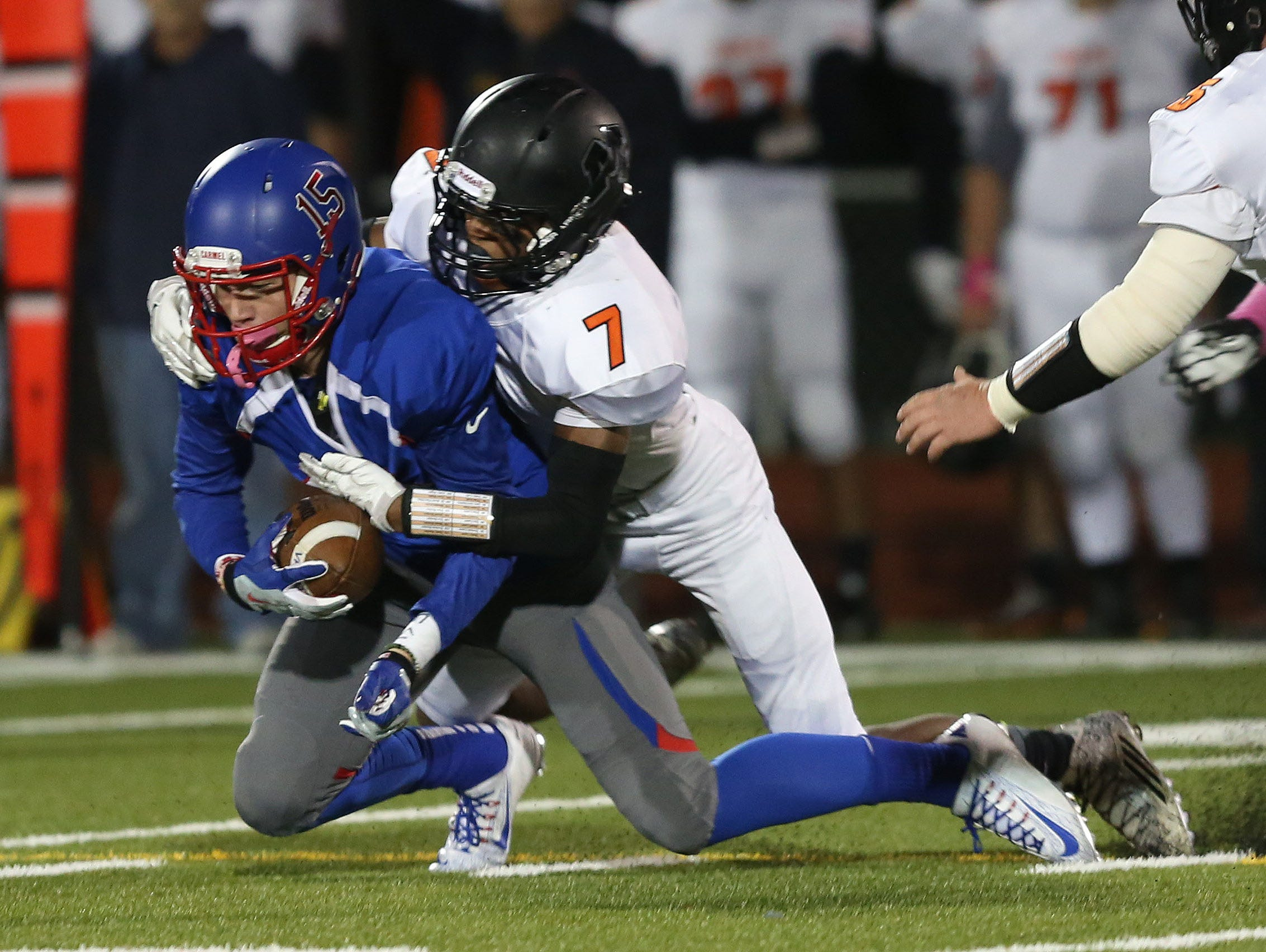 Carmel's Ryan Sullivan (15) gets tackled by Mamaroneck's Julian Haughton (7) after a first half catch and run during a boys football playoff game at Carmel High School Oct. 16, 2015.