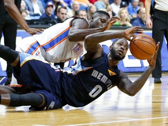 Memphis Grizzlies forward JaMychal Green (0) passes the ball to a teammate in front of Oklahoma City Thunder guard Victor Oladipo (5) in the third quarter of an NBA basketball preseason game in Tulsa, Okla., on Thursday.