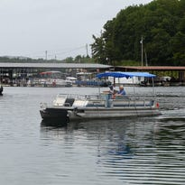 An employee at Bull Shoals Lake Boat Dock shuttles a boat owner to his dock on Wednesday, June 17, 2015.