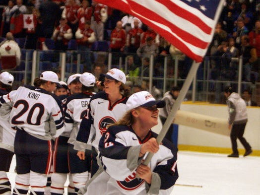 USA's Angela Ruggiero holds up an American flag following the gold medal win against Canada during their finals match at the XVIII Winter Olympics in Nagano, Japan, Tuesday, Feb. 17, 1998. USA won 3-1.