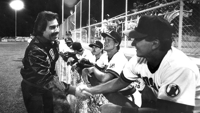 Singer Tony Orlando shakes hands with members of the Class A Palm Springs Angels after singing the National Anthem in the team's 1986 home debut.