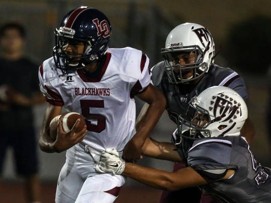 La Quinta quarterback Christian Egson carries the ball for a gain against Rancho Mirage on Friday, September 8, 2017 in Rancho Mirage.