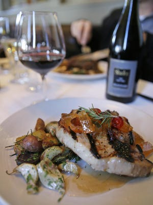 Grilled Berkshire pork chop with roasted potatoes, garlic and mostarda di frutta is paired with a glass of with Shafer Merlot wine at the Bistro Don Giovanni restaurant in Napa, Calif.