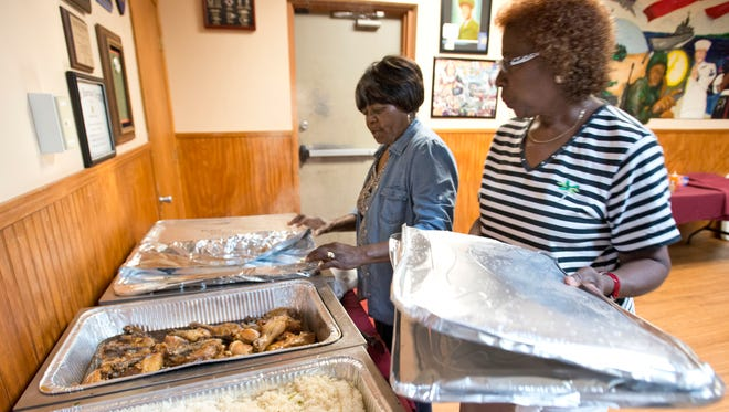 American Legion Post 193 Ladies Auxiliary members Bessie Bradshaw, right, and Olevia Wherry, left, put out food for the Postâ??s weekly luncheon Tuesday June 24, 2014.