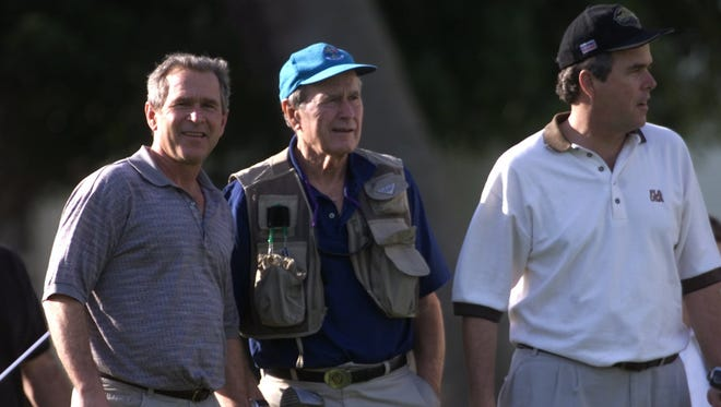 President elect George W. Bush, left, plays a round of golf with his brother Jeb on Dec. 27, 2000 with former president George Bush Sr. in tow at The Gasparilla Inn golf course on Boca Grande. ANDREW WEST/The News-Press