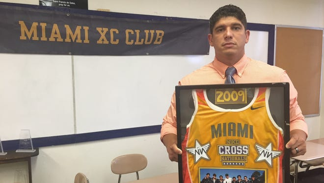 Bishop Verot coach Jorge Fleitas holds his Miami Columbus team's jersey from their 2009 Class 4A championship.