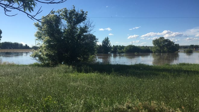 The Sun River edges closer to flooding Charlie and Missy Heit's property Wednesday at Manchester.