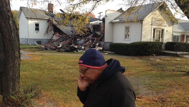 The Rev. Thomas Priest Jr. talks with a congregant by phone while surveying the damage of the thrift shop run by Redeemer United Methodist Church in Harper Woods.