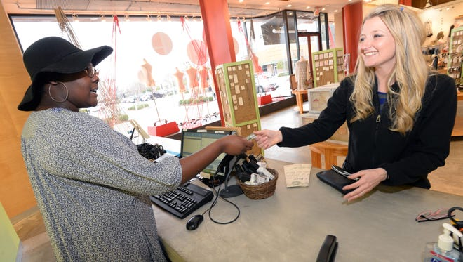 Erin Curren (left) hands Emily Lawrence her credit card while paying for her items at Altar'd State in the Shops at Bellemead. According to the 2015 State Business Tax Climate Index, Louisiana sales tax rates 50th.