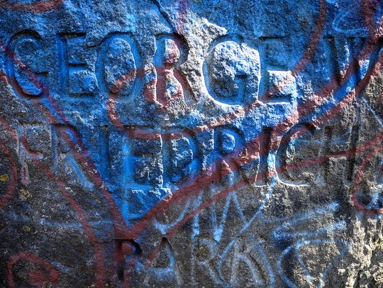 Graffiti covers the engraved sign at the entrance to