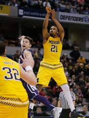 Michigan's Zak Irvin (21) and Northwestern's Bryant McIntosh (30) watch the ball as Irvin makes a game winning shot during the overtime.