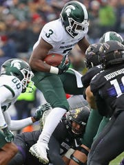 LJ Scott leaps over Northwestern defenders on Saturday,