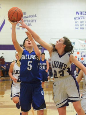 Yerington's Jordan Bobrick gets a few fingertips on a shot by Smith Valley's Mattie Johns during Smith Valley's non-league win Feb. 11. Both teams are seeking State Tourney berths at regional tournaments this weekend.
