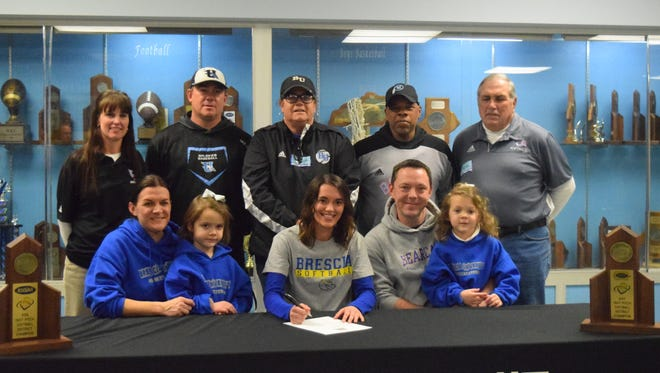 Annaclaire Johns, surrounded by family and coaches, signs to play collegiate softball at Brescia University.