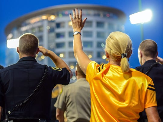 Fans and policeman salute the Iowa Children's Hospital at the end of the first quarter during the game between the Iowa Hawkeyes and the Penn State Nittany Lions at Kinnick Stadium.