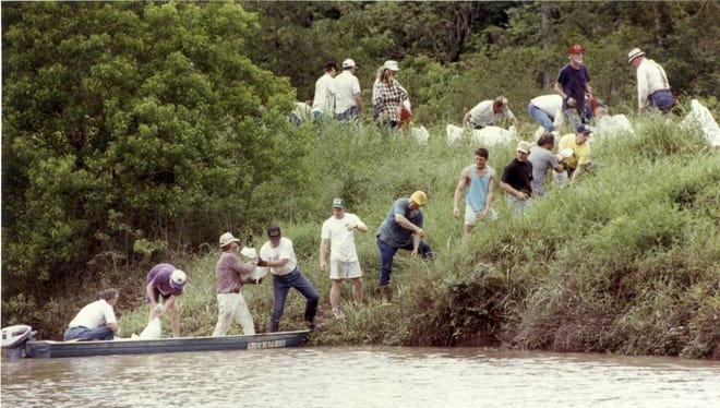 Town and Country residents sandbag the levee between the subdivision's drainage canal and canal L-11 in an effort to keep L-11 from running over its banks in May 1991. The sandbags had to be transported to the levee by boat and the canal was already overflowing the levee by mid-morning. About 85 residents and volunteers showed up to sandbag. Members of the Louisiana Tech football team joined the sandbag brigade, loading sandbags into the boats.